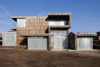 Maison façade recouverte de planches recyclées de bobines en bois