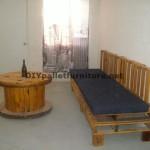 Un canapé avec des palettes et une table avec une bobine en bois