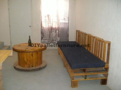Un canapé avec des palettes et une table avec une bobine en bois 1