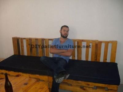 Un canapé avec des palettes et une table avec une bobine en bois 2