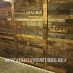 Mur tapissé de planches de palettes et crochets